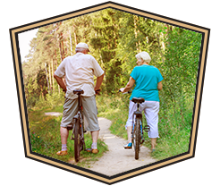 older couple on bikes in the forest