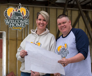 welcome home owners standing in front of build site