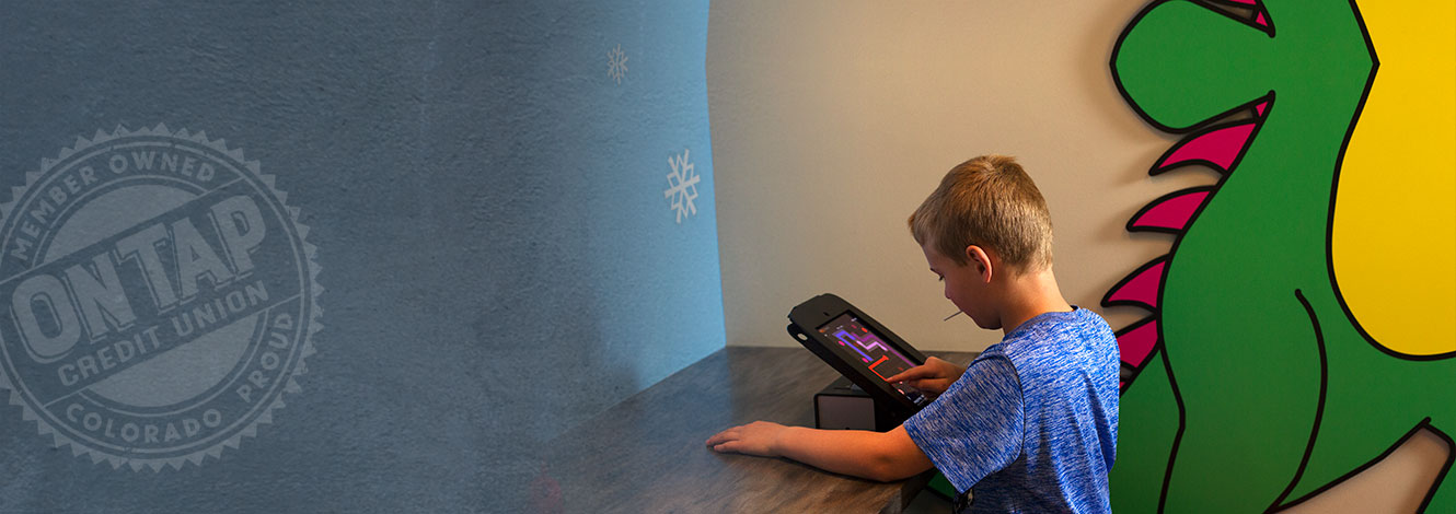 boy playing on tablet in brewster room at branch