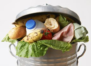 Household garbage bin overflowing with produce and other food