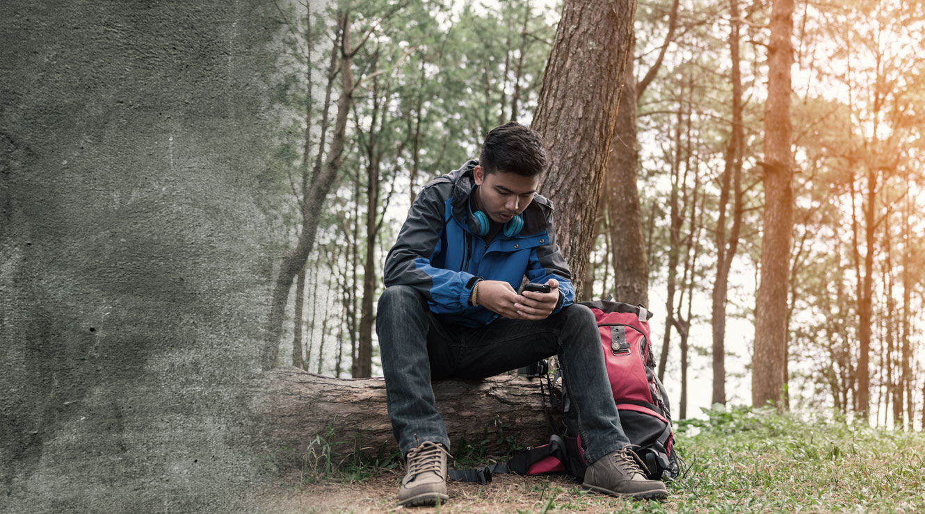 man sitting in woods looking at mobile phone