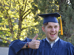 Male college graduate in cap and gown with thumbs up gesture.