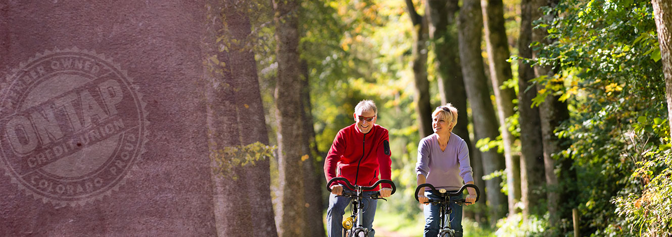 older couple biking in wilderness