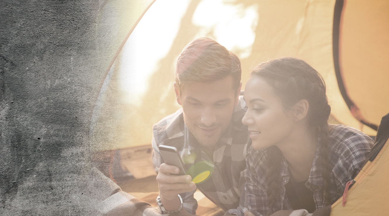 couple in tent looking at mobile device
