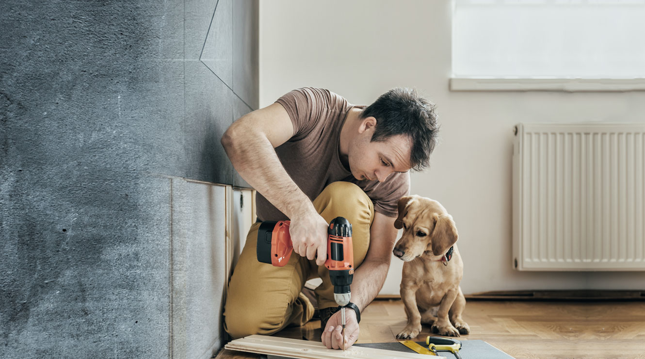 man with drill working on home next to dog